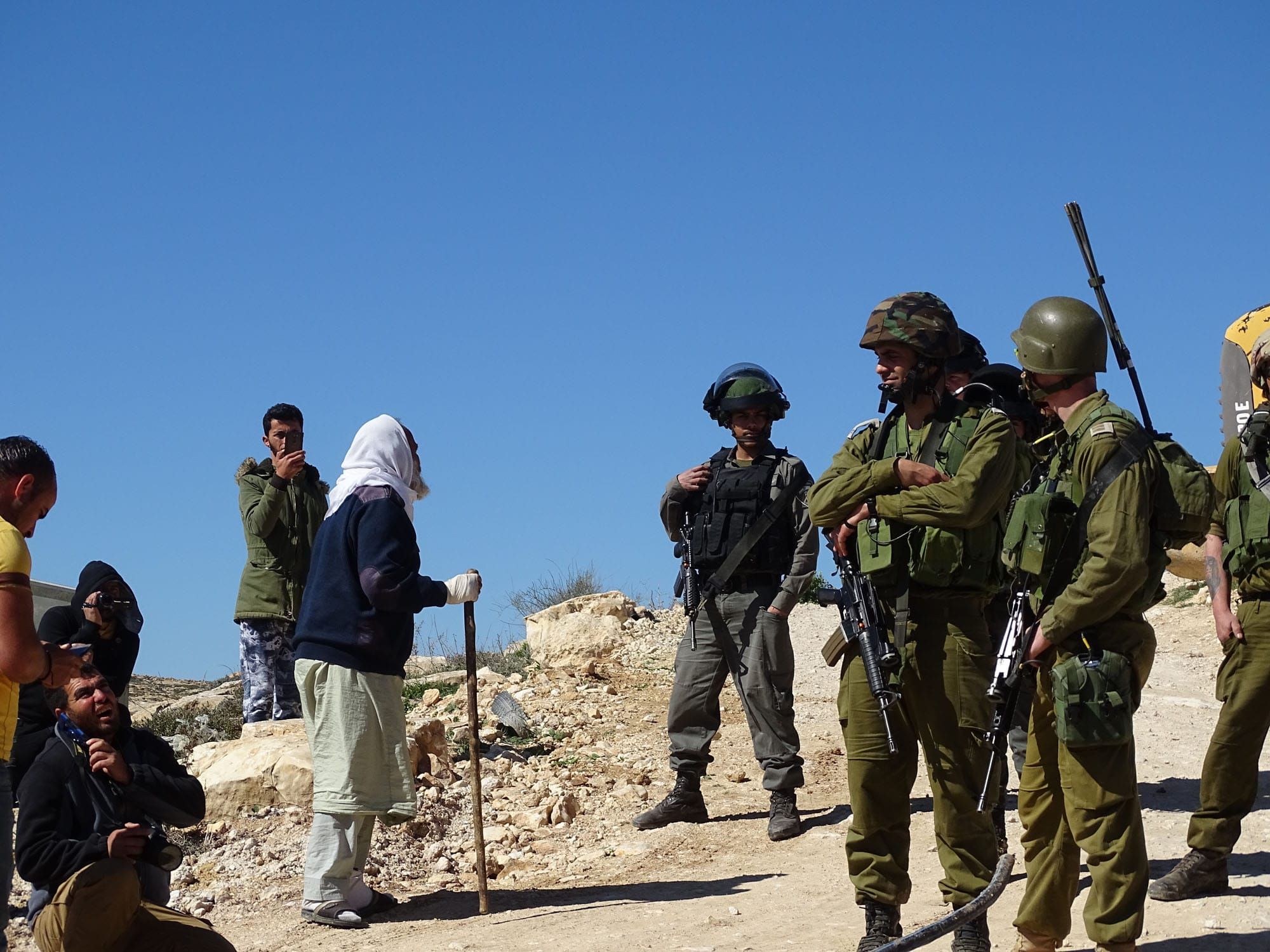 A Palestinian shepherd complains to Israeli soldiers as community water pipes are destroyed